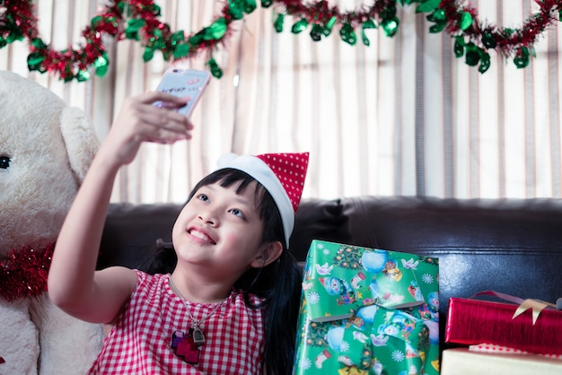 クリスマスのサンタクロースの帽子をかぶったアジアの少女がビデオ通話のためにスマートフォンを見る