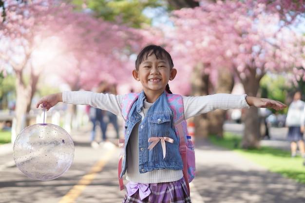 花の桜の木の下の庭でアジアの小さな女の子