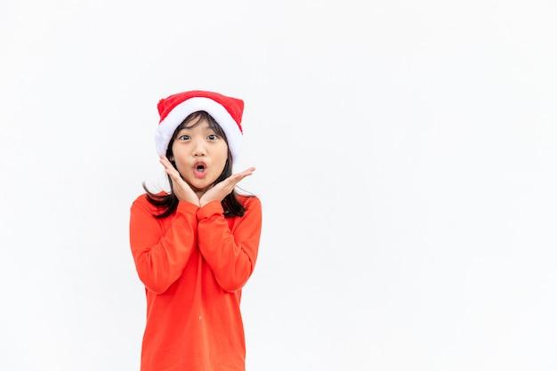 흰색 바탕에 빨간 산타 모자에 아시아 어린 소녀.