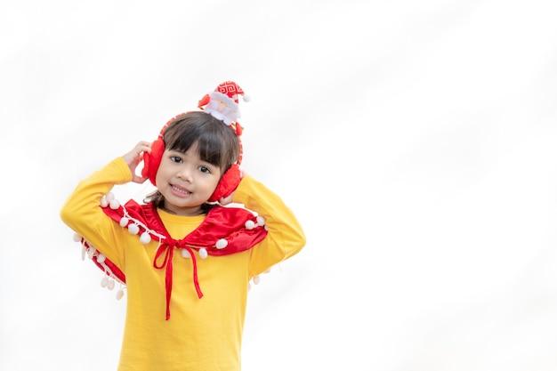 Азиатская маленькая девочка в красной шляпе санта на белом фоне.
