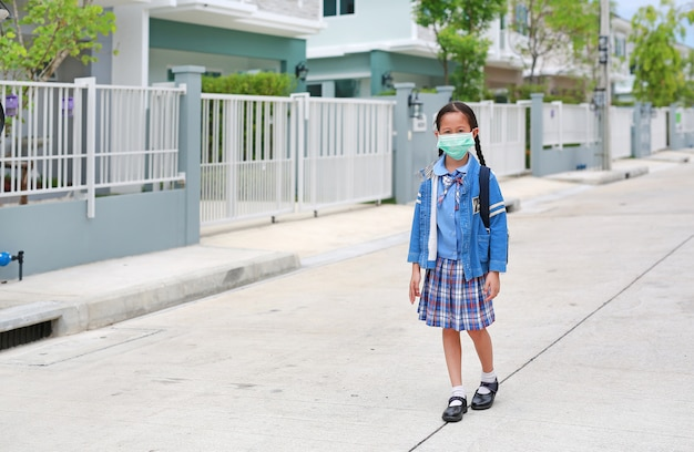通りを歩いて医療マスクを身に着けている制服でアジアの少女
