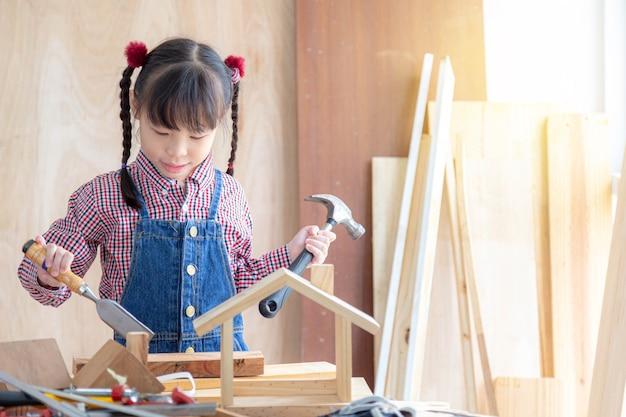 アジアの少女は、木工所で木造住宅を設計、建設しています。学習、家族、活動の概念。