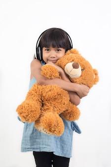 アジアの少女は孤立したテディベアを抱いています