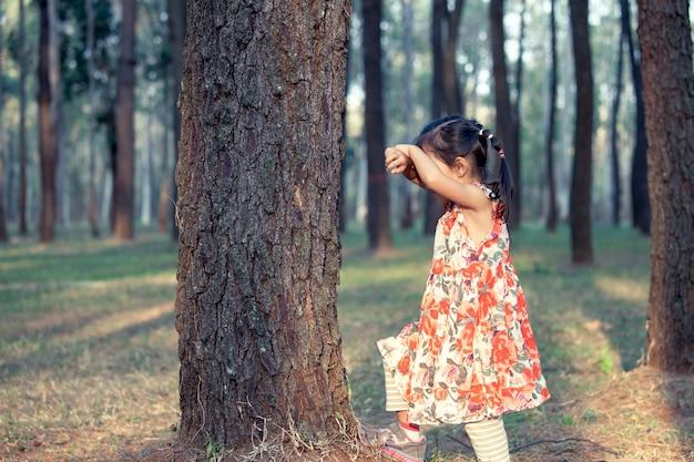 アジアの少女は公園に隠れて隠れている顔を演奏しています