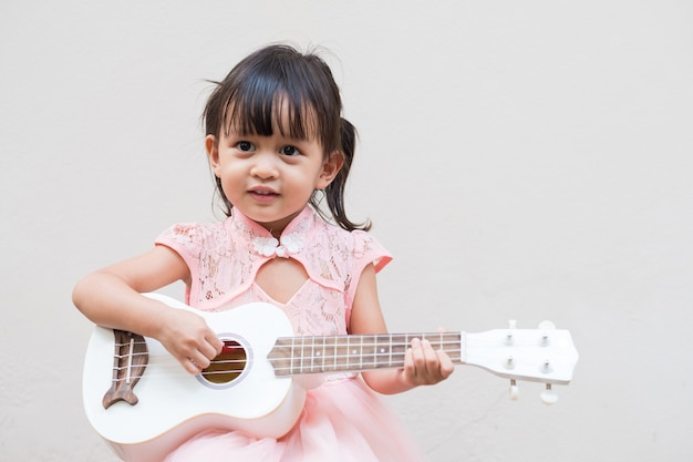 Asian little girl is playing ukulele with fully happiness moment