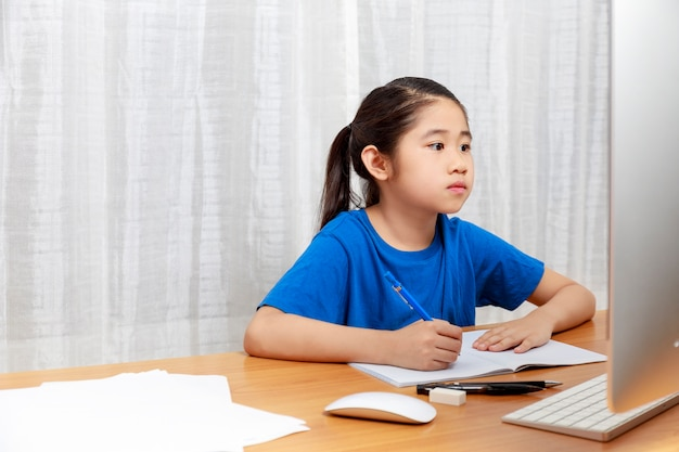 Asian little girl is studying online via the internet  sitting and writing in  living room at home. asia children writeing with pencil on notebook. online learning at home or learn frome home concept.