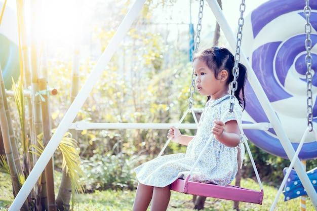Asian little girl is swinging in the backyard