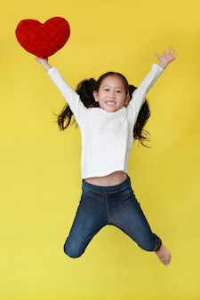 Asian little girl jumping and holding a red heart in one hand on yellow background