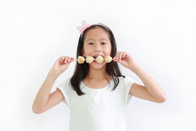 카메라를 보고 배경에 고기 공 스틱을 먹는 아시아 어린 소녀 아이