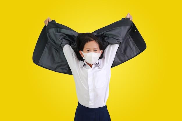 보호용 얼굴 마스크를 쓴 흰색 셔츠를 입은 아시아계 어린 소녀가 정장을 벗고 노란색 배경에 격리된 손을 들어 올립니다. 클리핑 패스가 있는 이미지