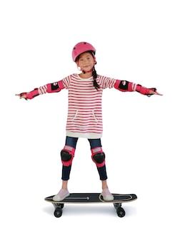 안전과 보호 장비를 착용한 아시아 어린 소녀 스케이트보더는 흰색 배경에 격리된 스케이트보드에 서 있습니다. 클리핑 패스가 있는 이미지.