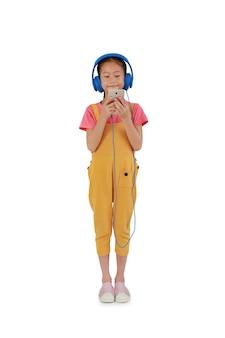 立っているアジアの小さな女の子の子供は、ヘッドフォンを着用し、白い背景で隔離のスマートフォンを再生します。クリッピングパスのある画像