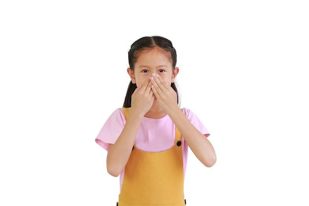 아시아 어린 소녀는 흰색 배경에 격리된 냄새 때문에 코를 덮는 손을 사용합니다.