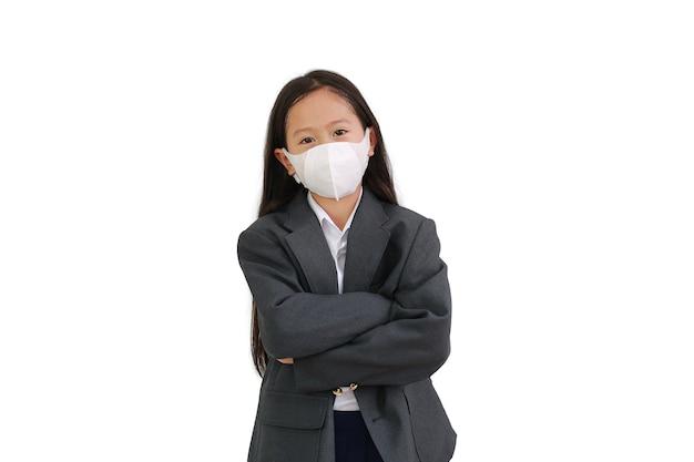 아시아계 어린 소녀는 정장 셔츠, 학생복, 보호용 안면 마스크를 착용하고 팔짱을 끼고 포즈를 취하고 흰색 배경에 격리된 카메라를 바라보고 있습니다.