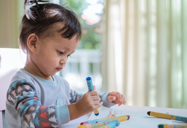Asian little girl learning to draw and paint with a crayon on the table
