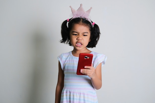 Asian little girl looking to her mobile phone with annoyed face expression