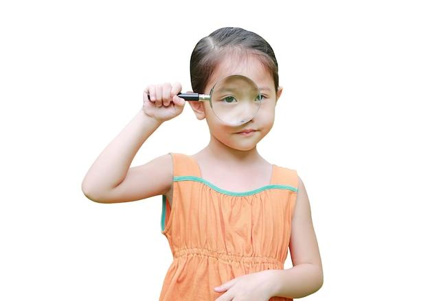 Азиатская маленькая девочка смотрит через увеличительное стекло, изолированное на белом