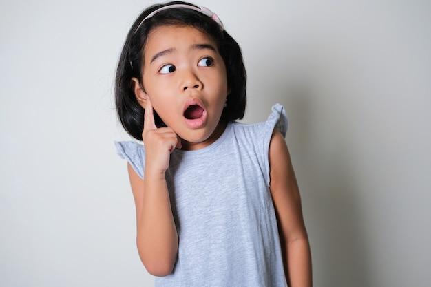 Азиатская маленькая девочка смотрит в сторону с подозрительным выражением лица
