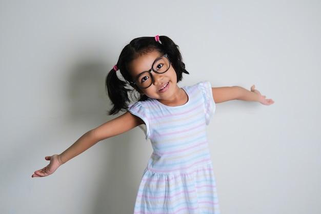 Азиатская маленькая девочка раскрывает руки и показывает счастливое выражение лица