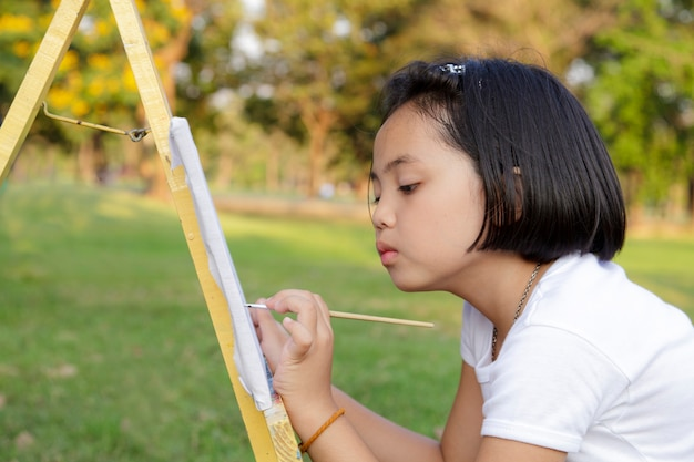 Asian little girl painting in in the park