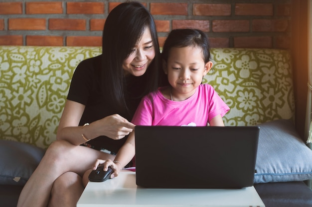 Asian little girl playing at laptop with her mother at home.
