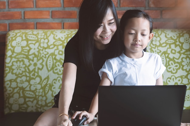 Asian little girl playing laptop with her mother at home.