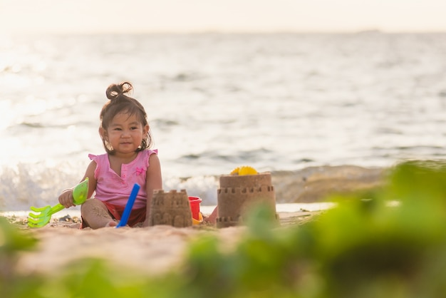 Asian little girl playing sand with toy sand tools at a tropical sea beach