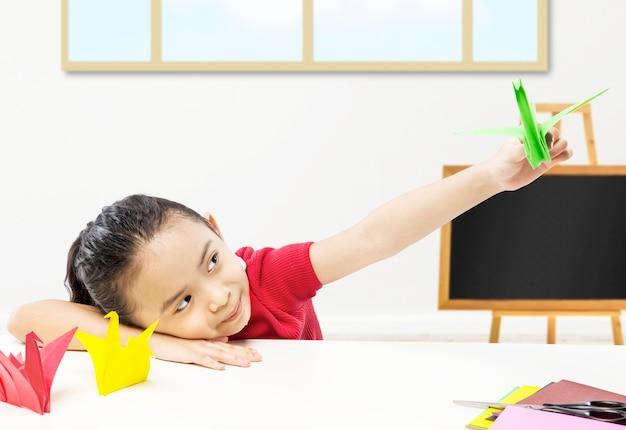 Азиатская маленькая девочка играет с гусиной бумагой в классе