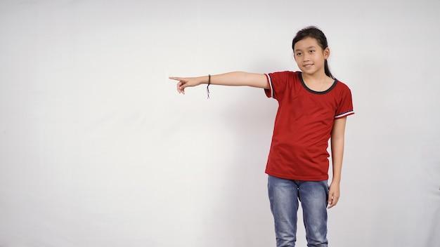 白い背景で隔離のアジアの少女を指しています