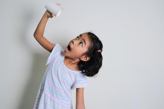 Азиатская маленькая девочка наливает пустой пластиковый стаканчик и показывает удивленное выражение