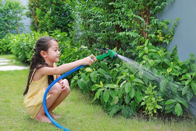 Азиатская маленькая девочка льет брызги воды на деревья