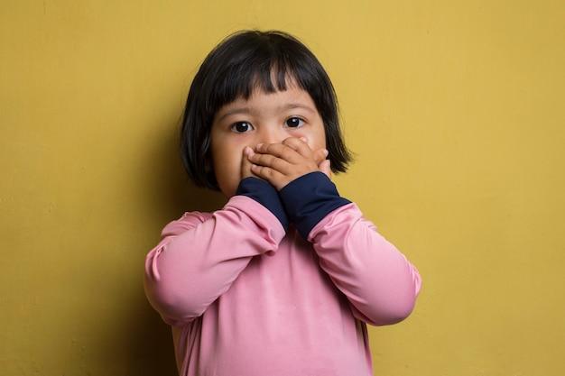 Азиатская маленькая девочка закрыла рукой рот (прикрыла) рот