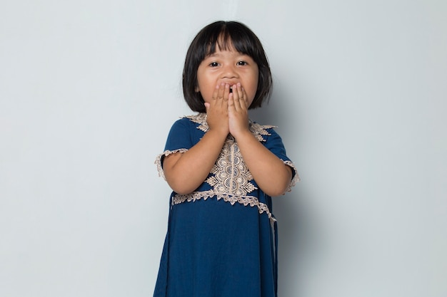 Asian little girl put her hand cover her mouth feeling surprise to something