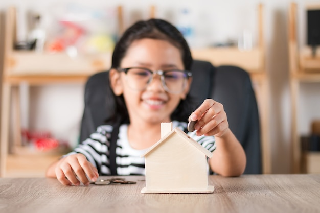 Asian little girl in putting coin in to house piggy bank