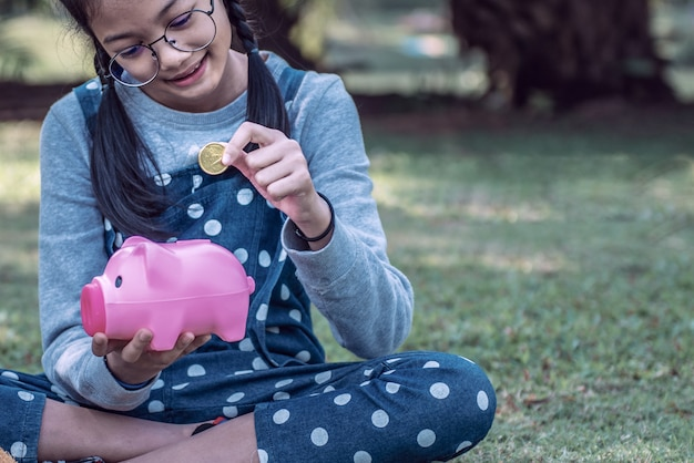 Asian little girl putting coin into piggy bank in the park.