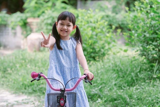 笑顔で幸せな彼女の外の自転車に乗ってアジアの少女