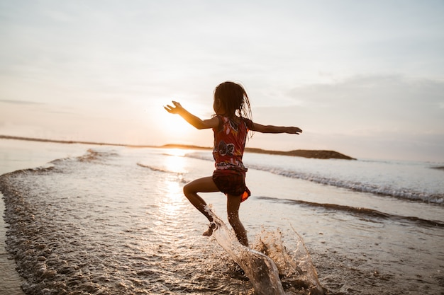 Asian little girl running and jump on the beach