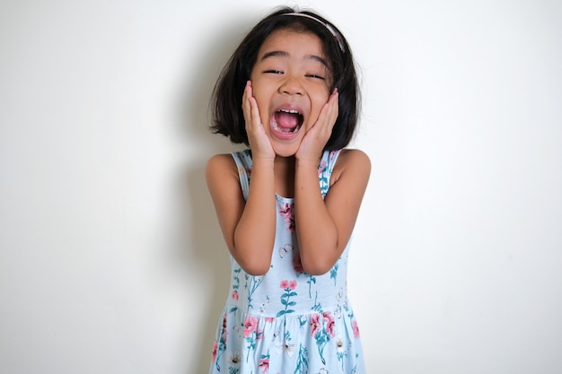 Asian little girl screaming excited while her hand touching cheek
