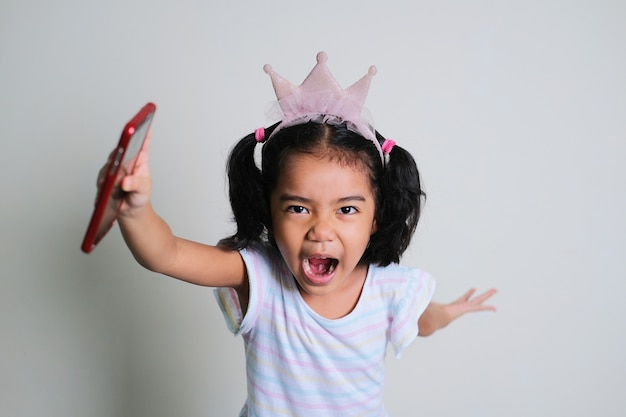 Asian little girl screaming while running forward with her hand holding mobile phone