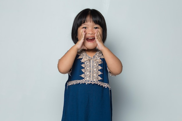 Asian little girl shouting and yelling announcing isolated on white background