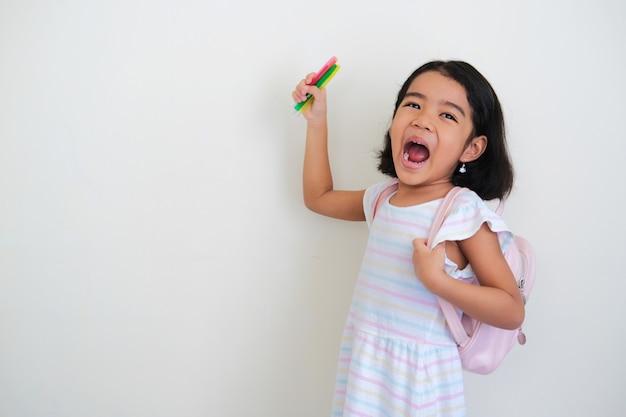 Азиатская маленькая девочка показывает возбужденное выражение лица, нося рюкзак и держа ручку-раскраску