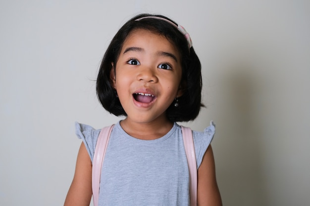 Asian little girl showing excited face expression while wearing her school backpack