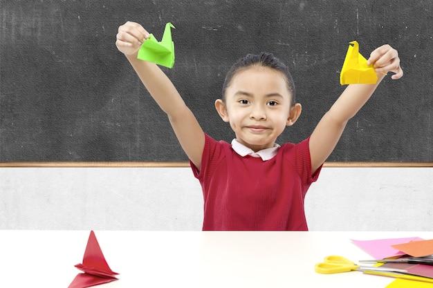 Азиатская маленькая девочка показывает свою гусиную бумагу в классе