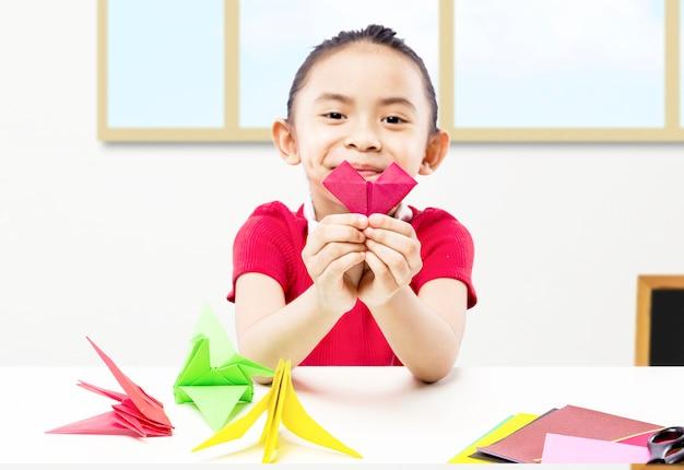 Азиатская маленькая девочка показывает свое бумажное ремесло в классе