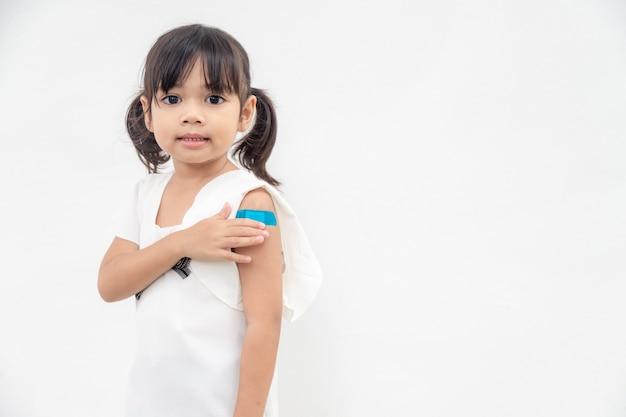 予防接種または予防接種を受けた後、腕を見せているアジアの少女