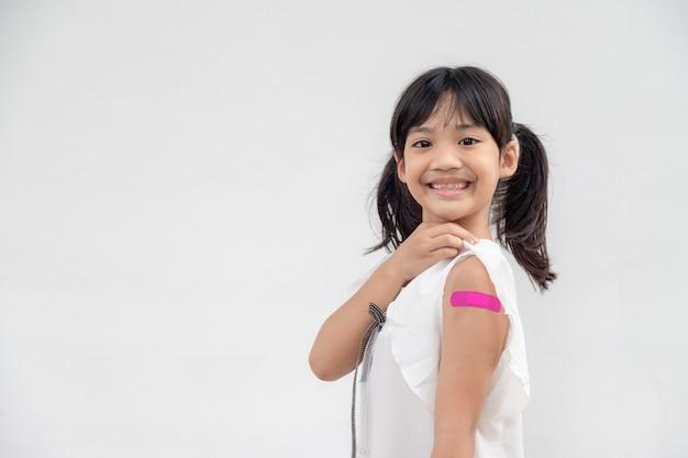 예방 접종 또는 예방 접종 어린이 예방 접종 후 팔을 보여주는 아시아 소녀
