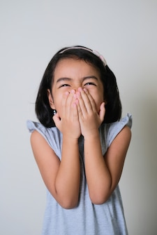 Asian little girl showing shy gesture with her hand cover mouth