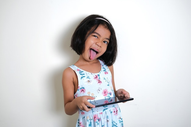 Asian little girl showing silly funny face while holding her mobile tablet gadget