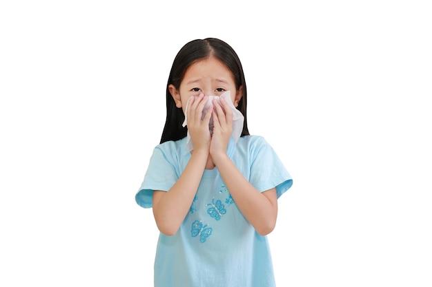 Азиатская маленькая девочка больна и чихает тканью на белом