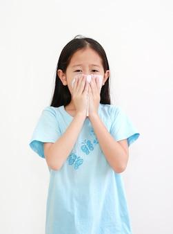 アジアの少女は、白い背景で隔離のティッシュペーパーで病気とくしゃみをします。